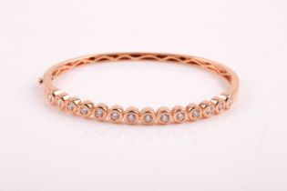 An 18ct rose gold and diamond bangle, the bracelet collet-set with round brilliant-cut diamonds of