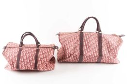 A vintage Christian Dior travel bag, with monogram pink and dark purple fabric and maroon leather