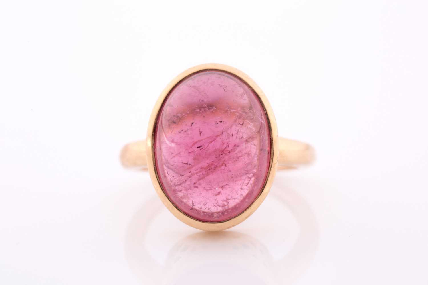 An 18ct yellow gold and tourmaline ring, set with an oval cabochon pink tourmaline, measuring