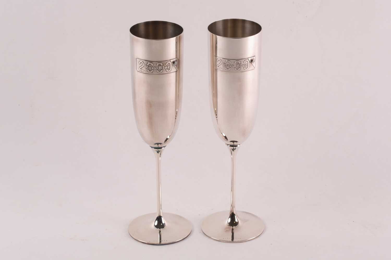 A pair of commemorative limited edition silver champagne flutes; with applied plaques reading '