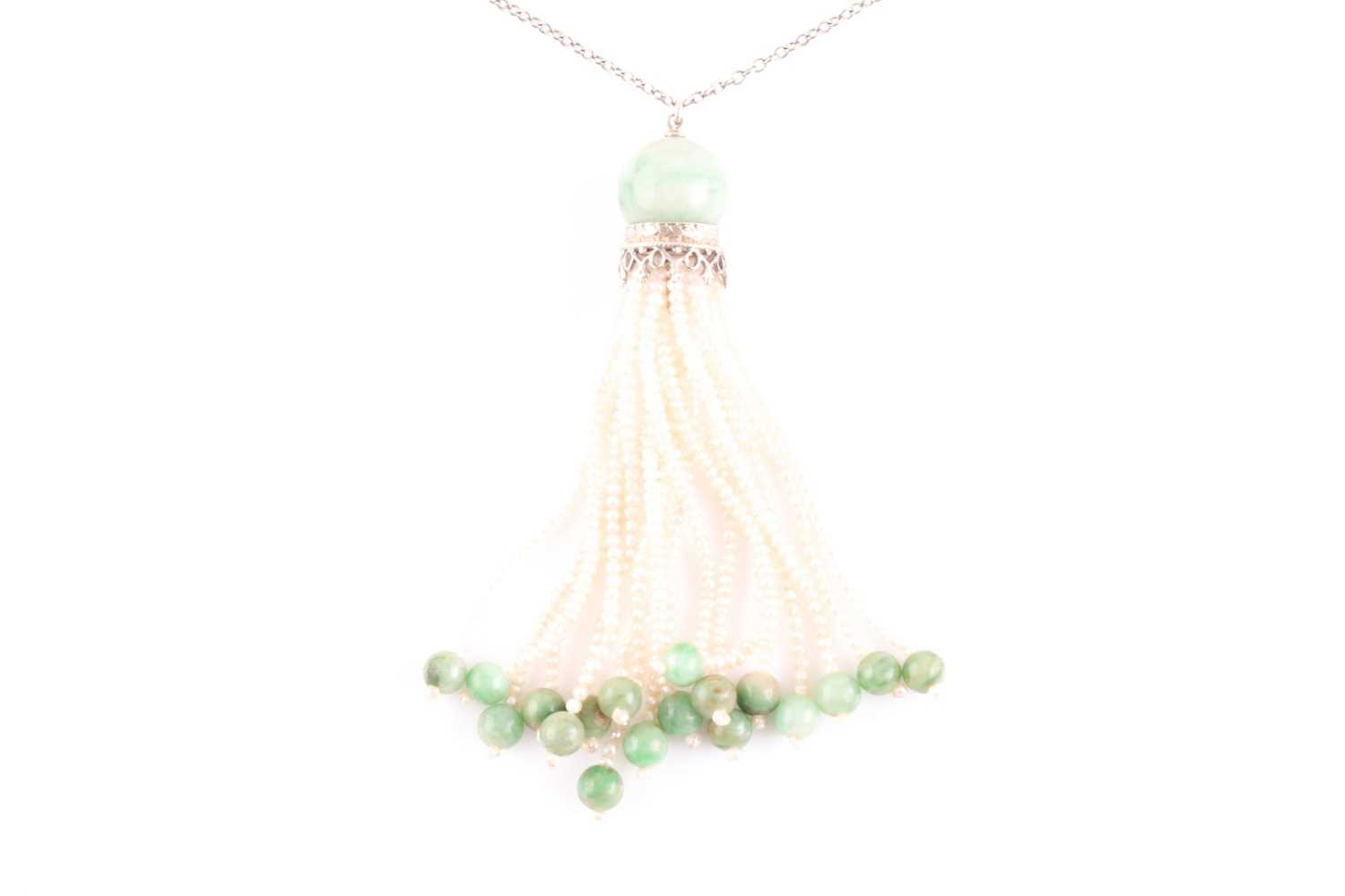 An Art Deco jade and seed pearl tassel pendant necklace, set with a rounded jade bead suspended with