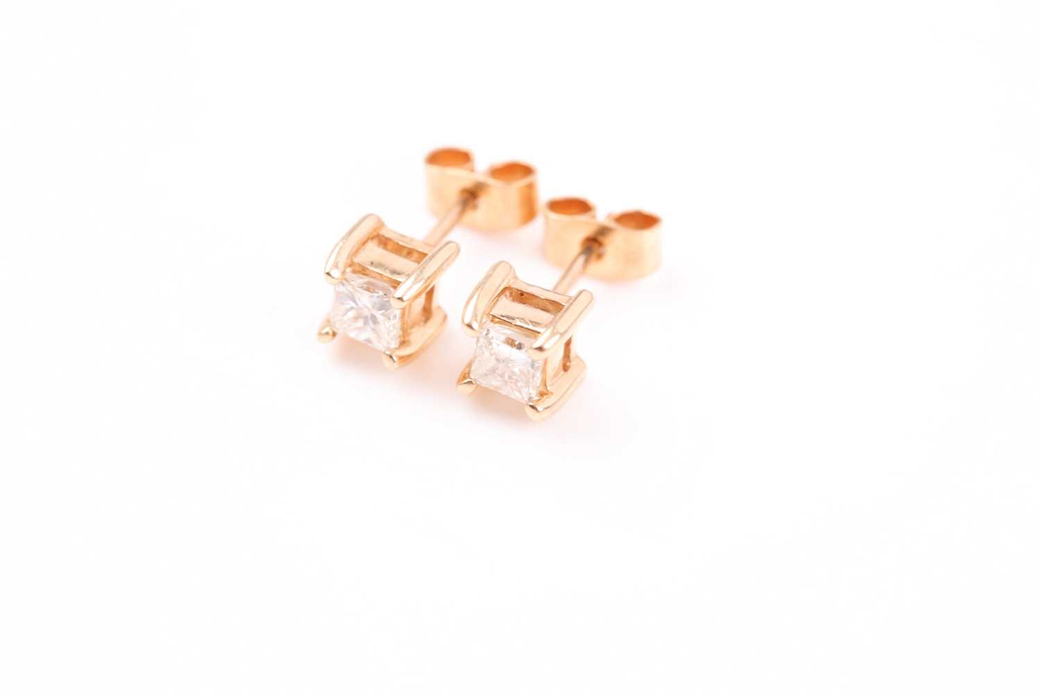 A pair of yellow metal and diamond earrings, set with square-cut diamonds of approximately 0.20 - Image 2 of 3
