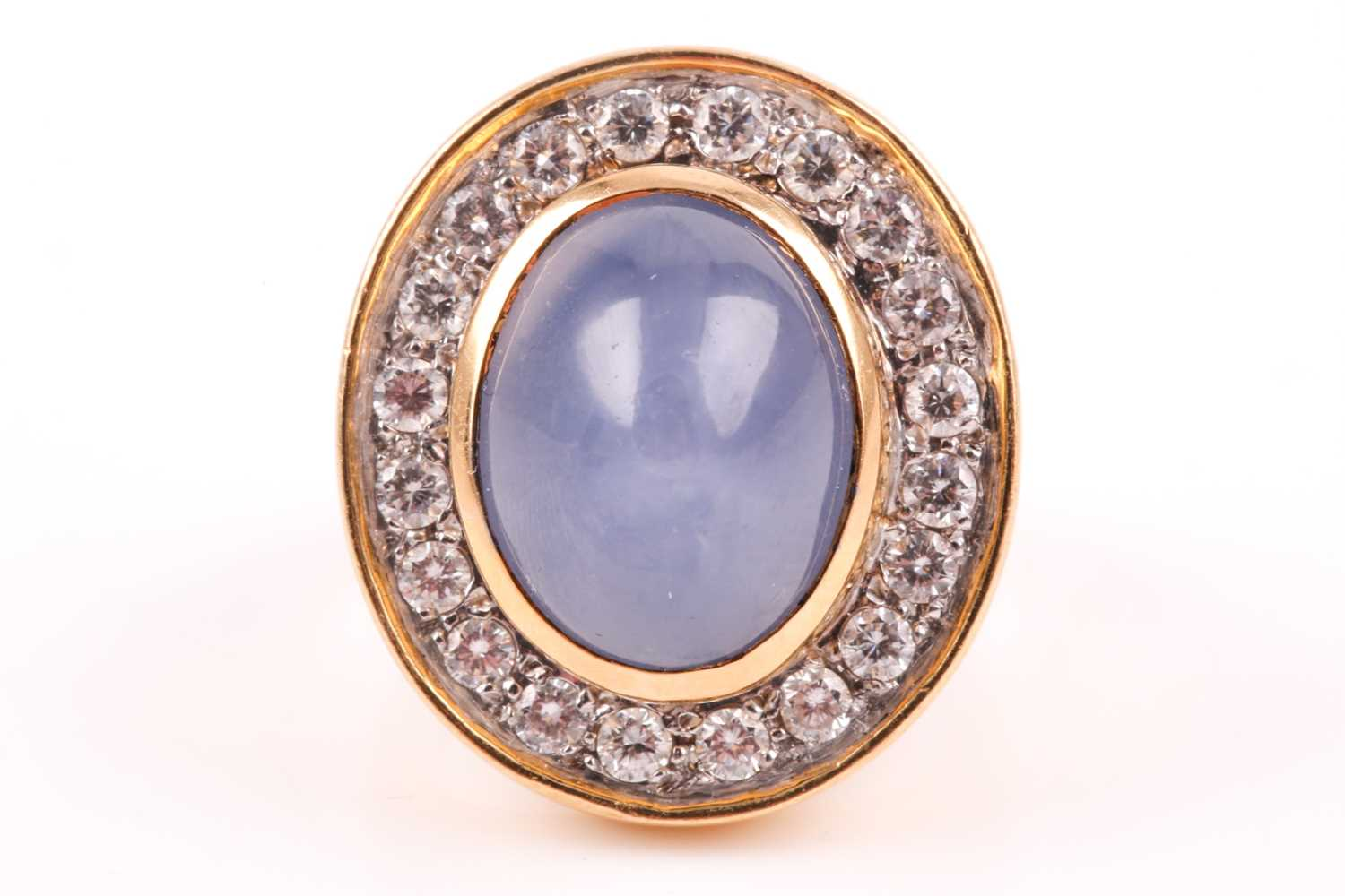 An 18ct yellow gold, diamond, and star sapphire cocktail ring, set with a domed cabochon sapphire,