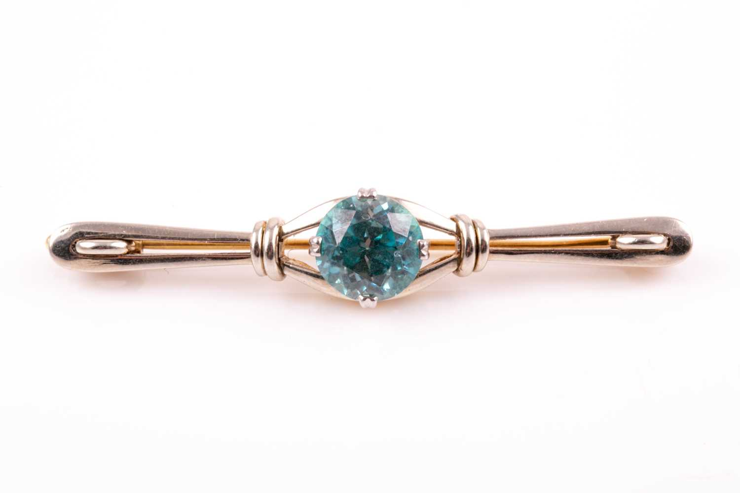 A white and yellow gold and blue zircon brooch, set with a mixed round-cut zircon measuring