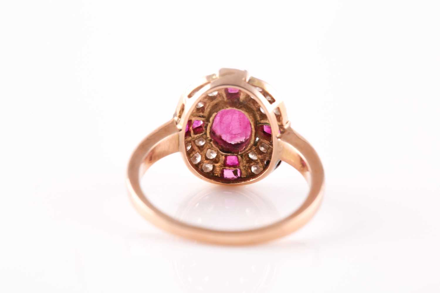 A ruby and diamond cluster ring, the central mixed oval cut ruby with a cruciform plaque of - Image 2 of 4