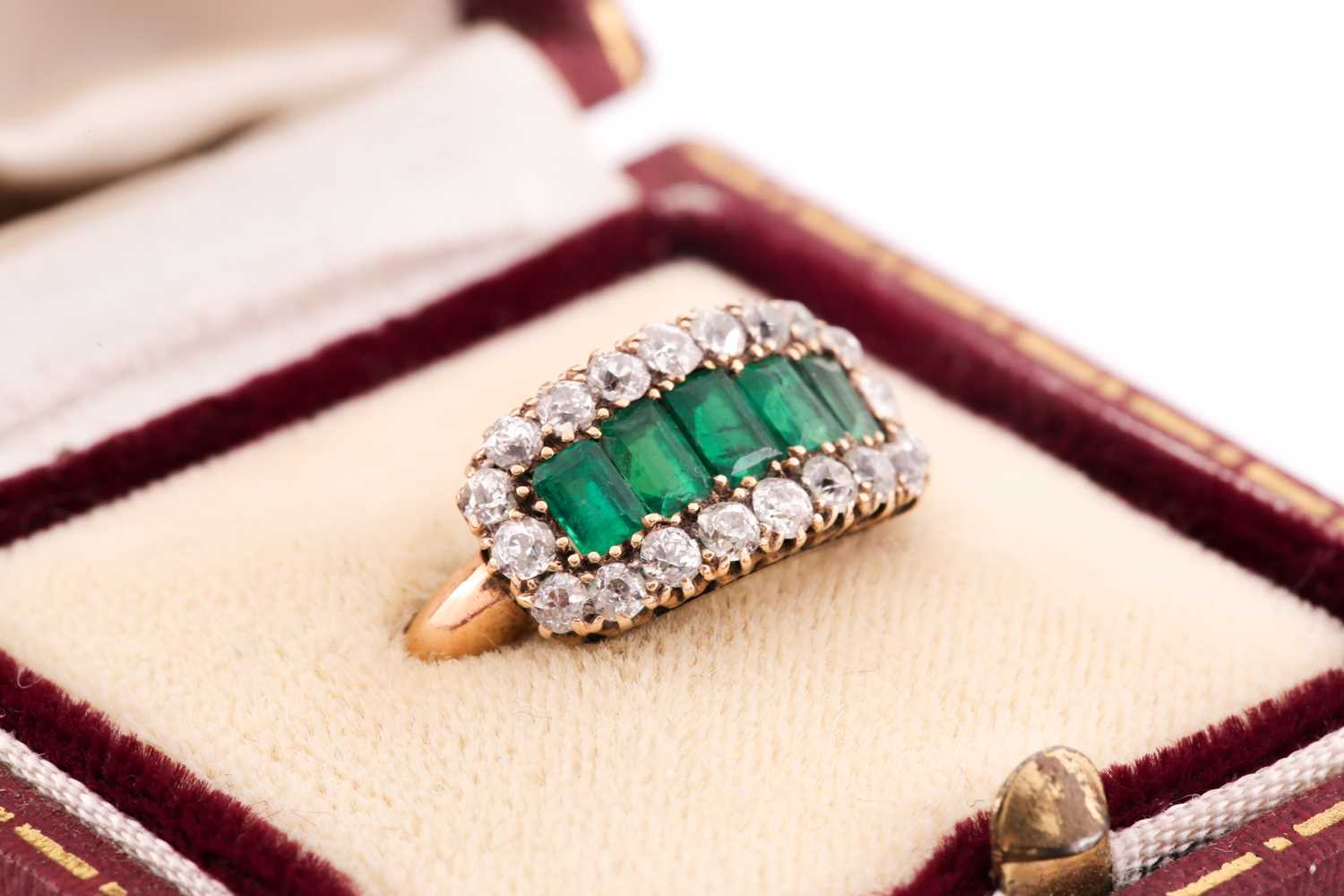 An emerald and diamond three row ring, set with a central line of slightly graduated emerald-cut - Image 2 of 6