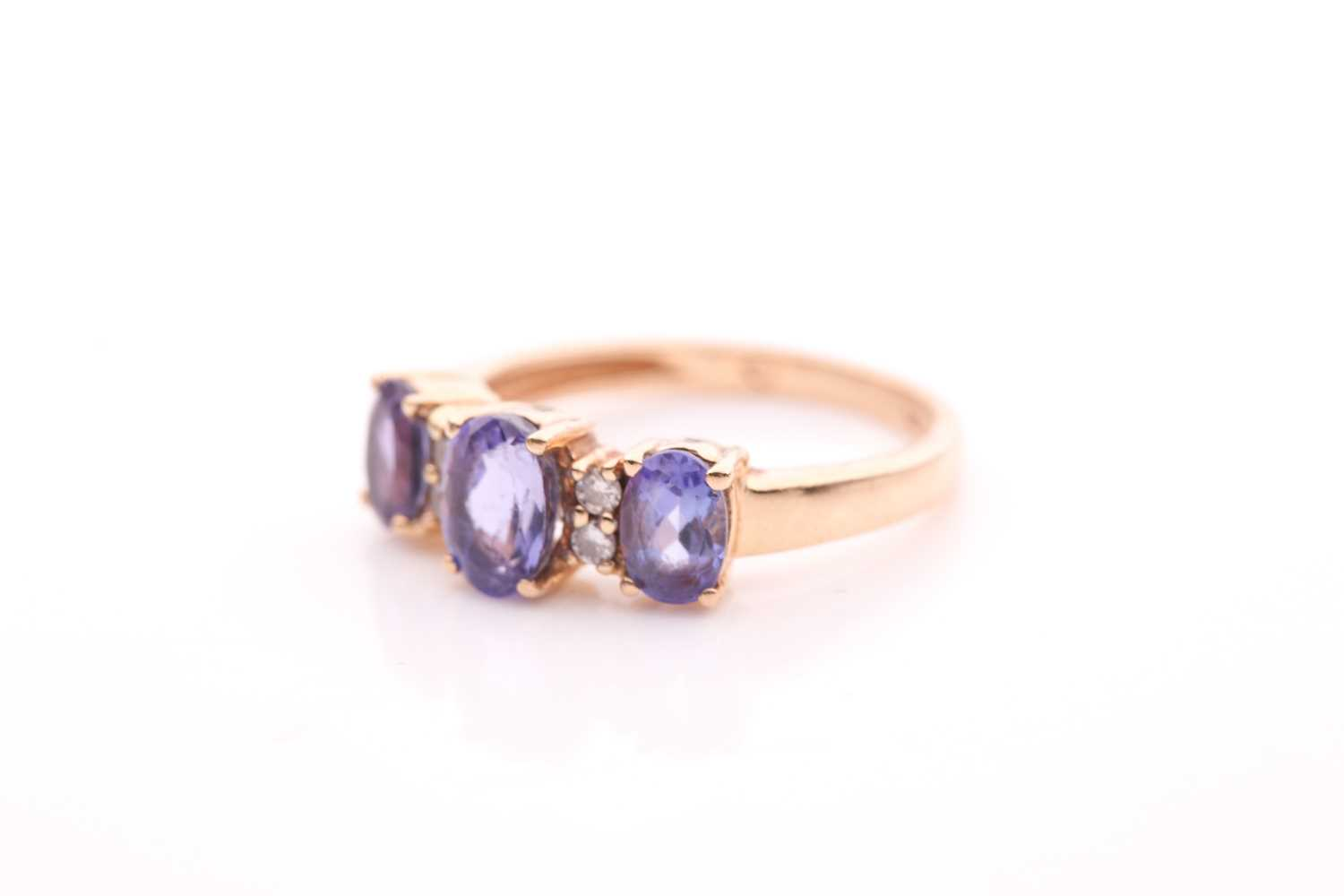 A yellow metal and tanzanite ring, set with three mixed oval-cut tanzanites, interspersed with - Image 4 of 5