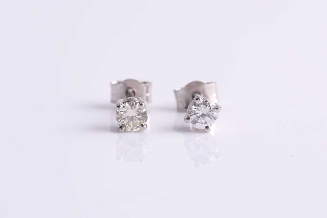 A pair of round brilliant-cut diamond ear studs, the diamonds of approximately 0.34 carats