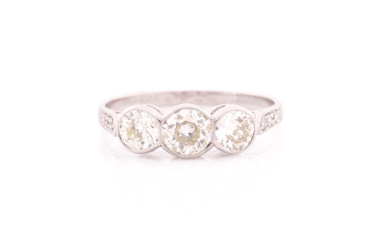 A platinum and diamond ring, collet-set with three old round-cut diamonds of approximately 1.35