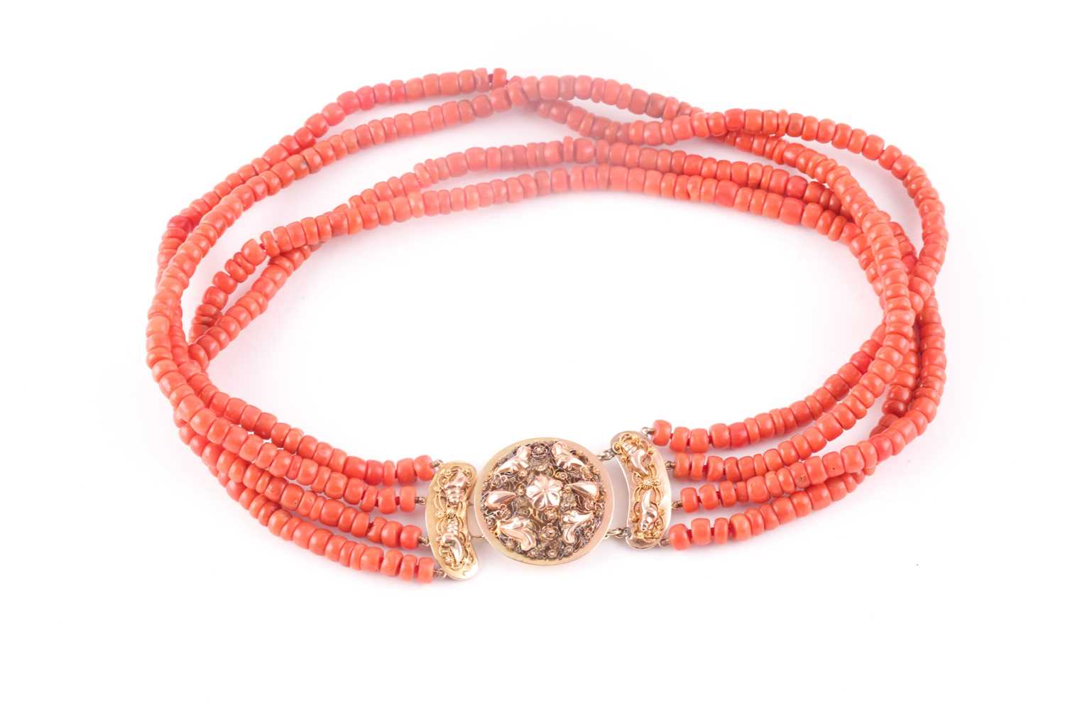A four strand coral choker necklace, fastened with a Continental yellow metal clasp, the roundel