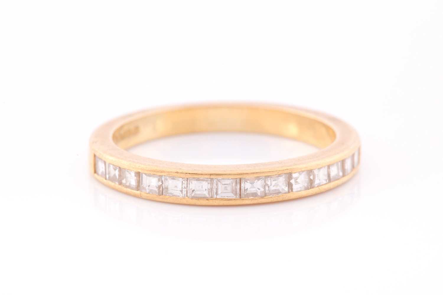 An 18ct yellow gold and diamond half-eternity ring the band calibre set with fourteen princess cut