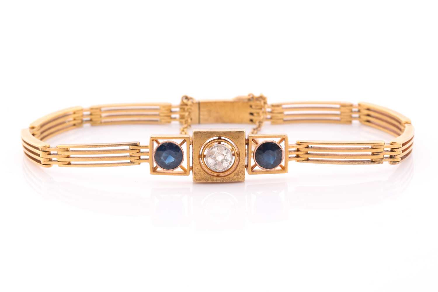 A yellow metal, diamond, and sapphire bracelet, set with a round-cut diamond of approximately 0.33