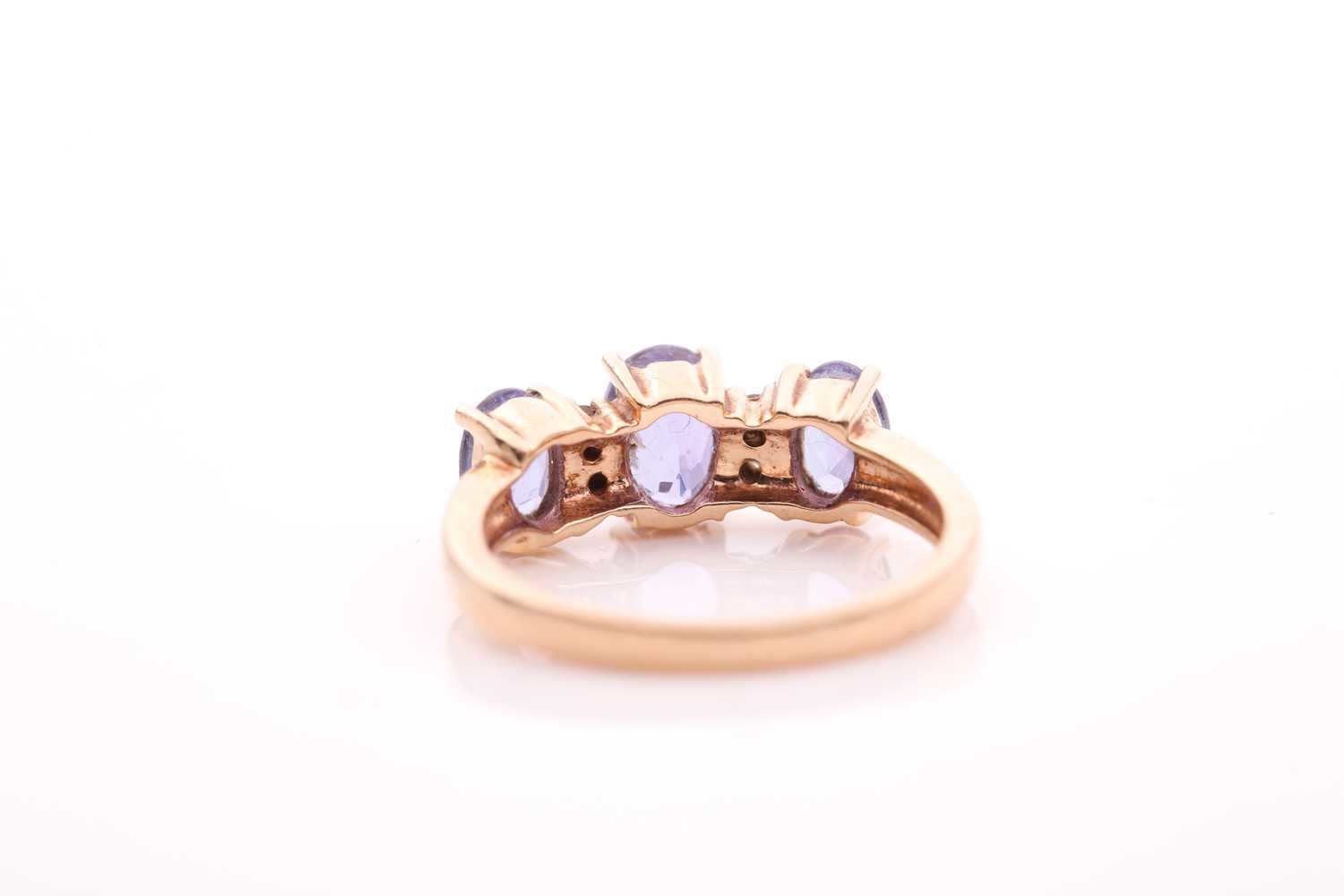 A yellow metal and tanzanite ring, set with three mixed oval-cut tanzanites, interspersed with - Image 3 of 5