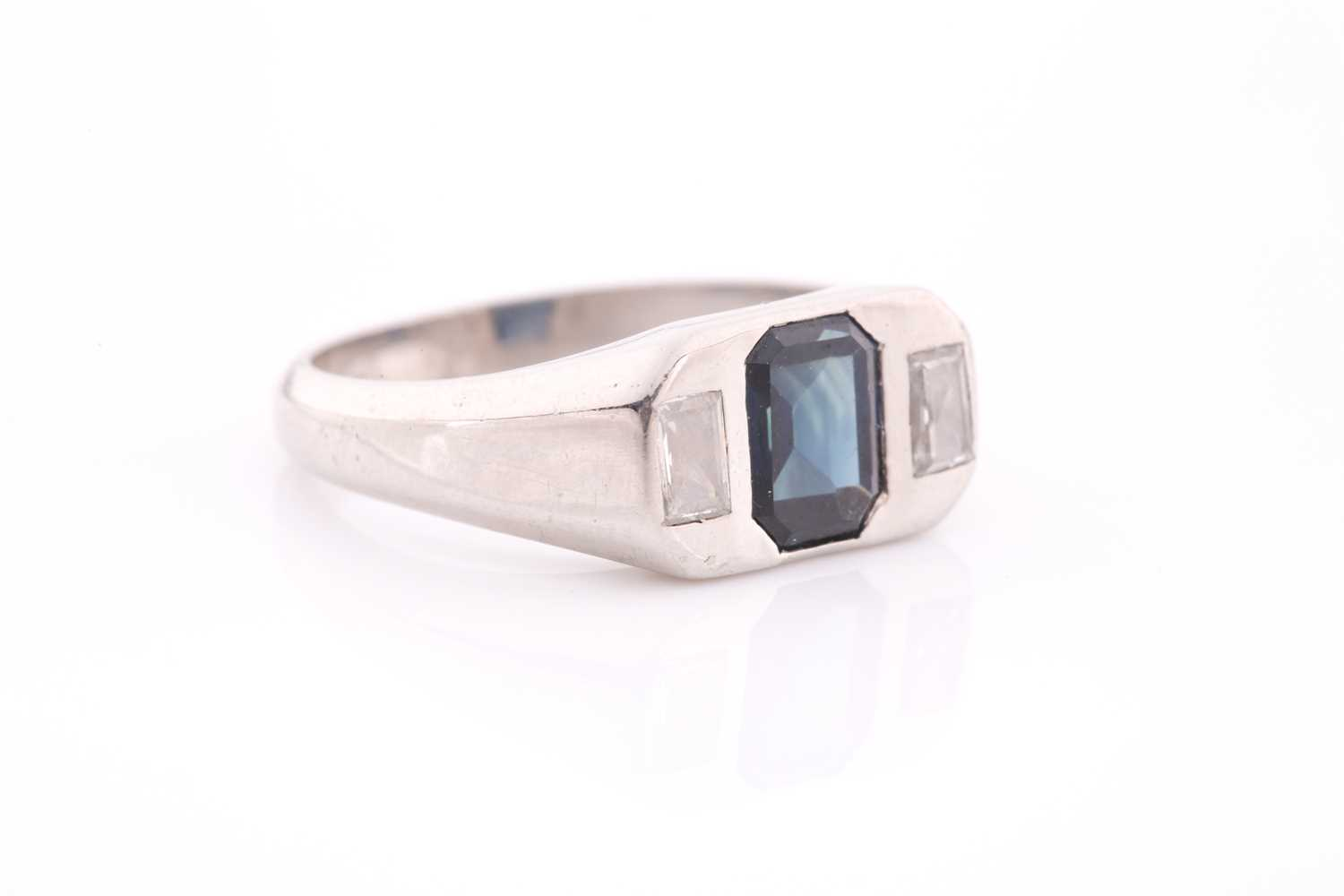 A diamond and sapphire ring, set with a mixed rectangular-cut sapphire, flanked with two modified - Image 2 of 4