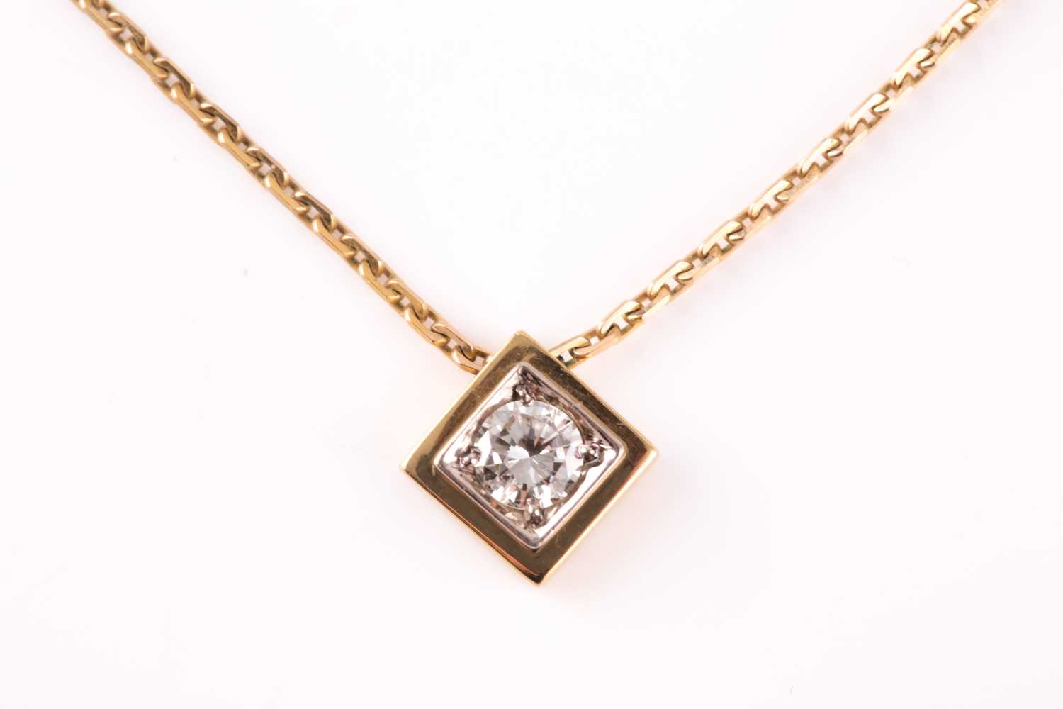 A solitaire diamond pendant, set with a round brilliant-cut diamond of approximately 0.33 carats,