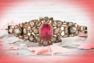 An antique yellow metal and diamond bangle, set with a reddish pink central stone, likely spinel,