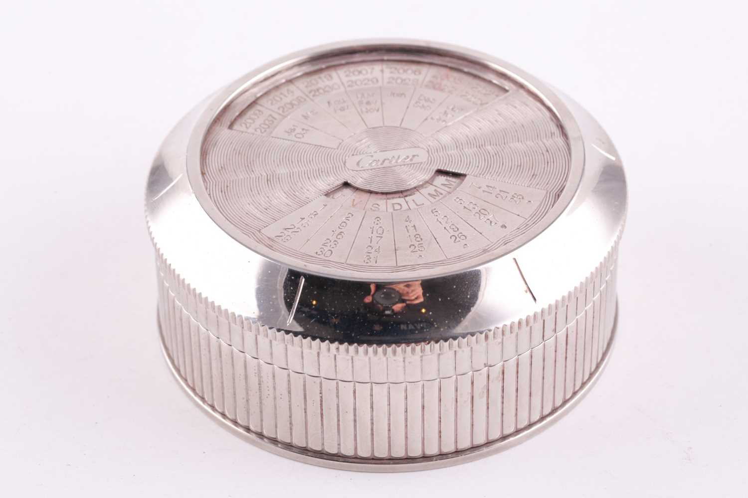 A Cartier chrome desk calender, with adjustable year, month, and date dial to lid, 8 cm diameter,