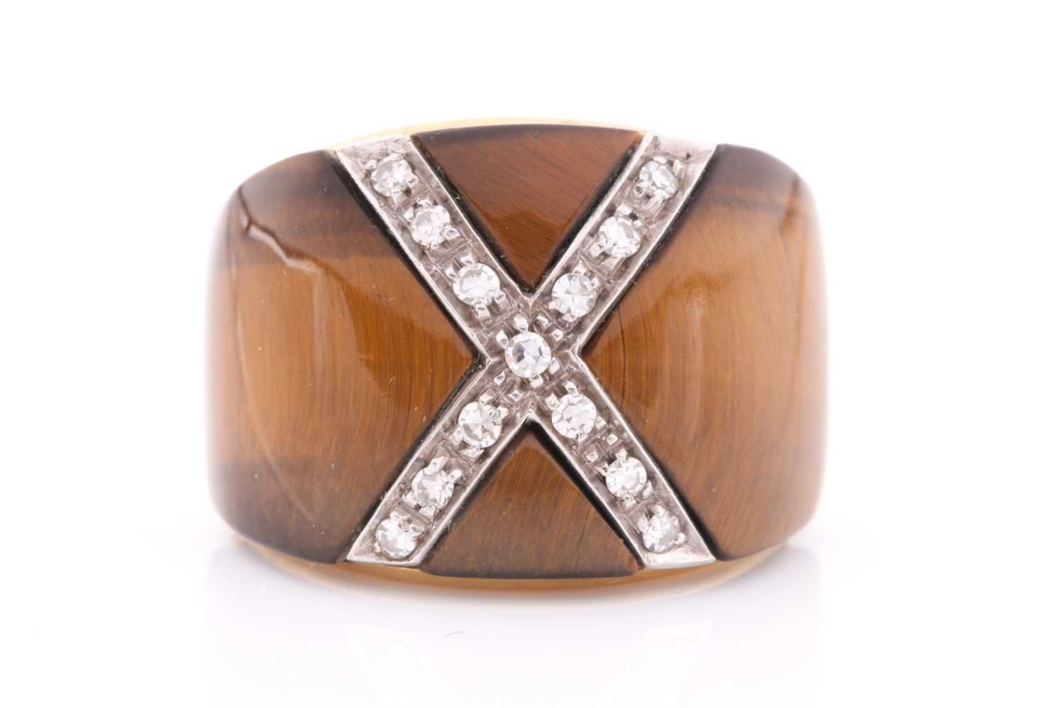 A yellow metal, diamond, and tigers eye cocktail ring, the wide band inset with a diamond-set cross,