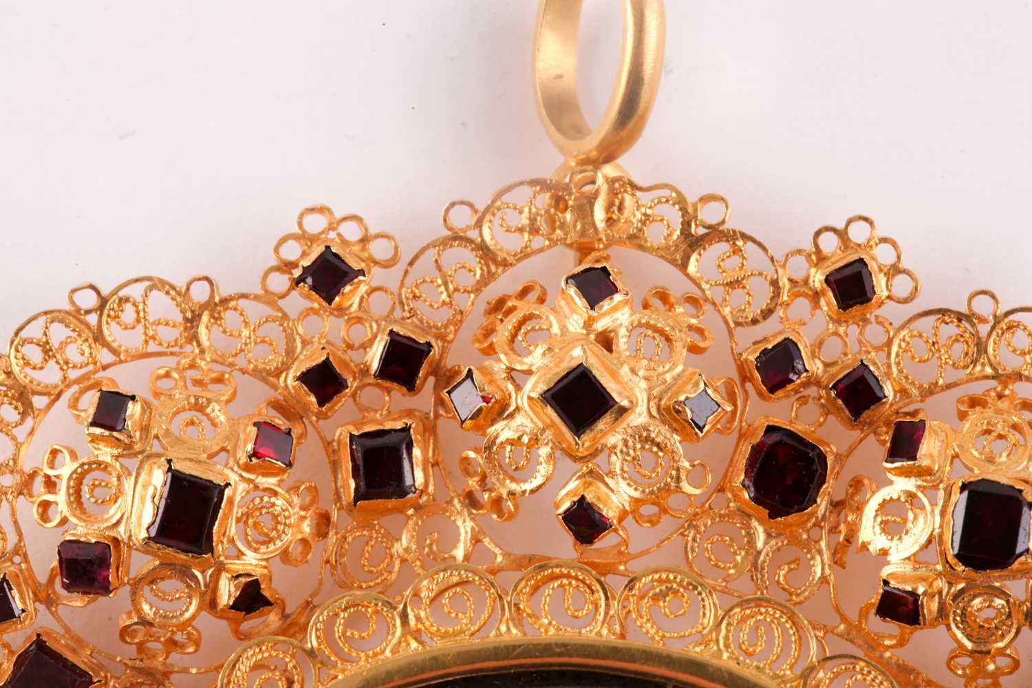 A Catalan gold and garnet pendant, centered with an oval glass aperture with faded paint, within - Image 2 of 3