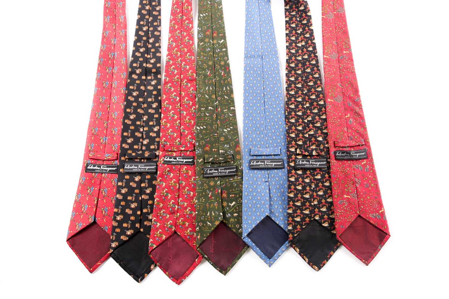 A group of seven Ferrogamo silk ties, various designs, in blue, red, green, and black silk. (7) - Image 2 of 2