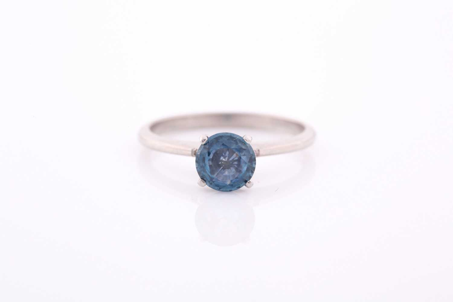 A platinum and solitaire sapphire ring, set with a mixed round-cut blue sapphire of approximately