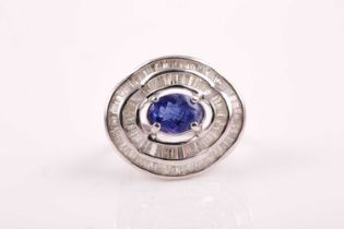 A silver, diamond, and tanzanite ring, set east to west with a mixed oval-cut tanzanite of