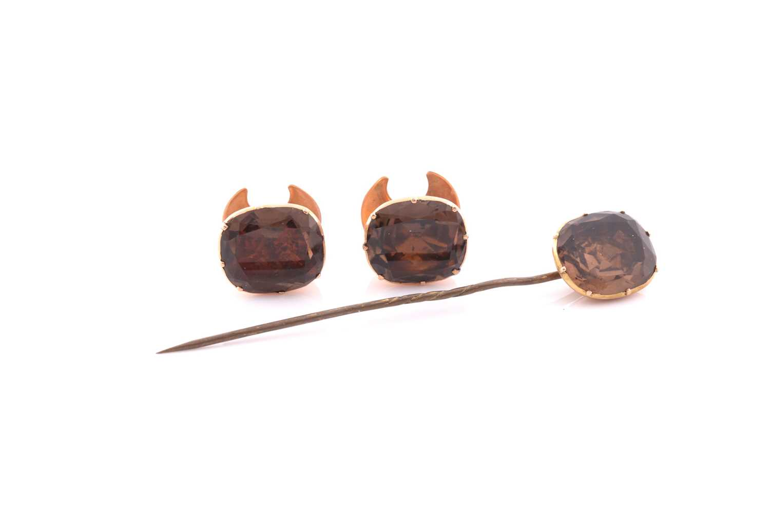 A pair of yellow metal studs set with foil-backed brown quartz, the stones measuring approximately