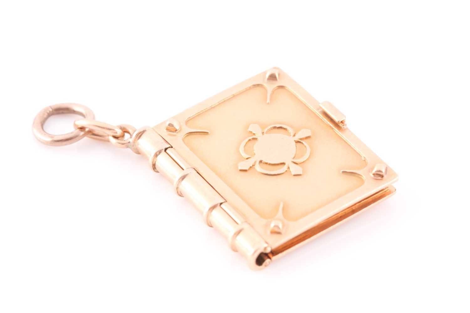 A yellow gold pendant in the form of a book, the hinged cover with quatrefoil decoration, opening to
