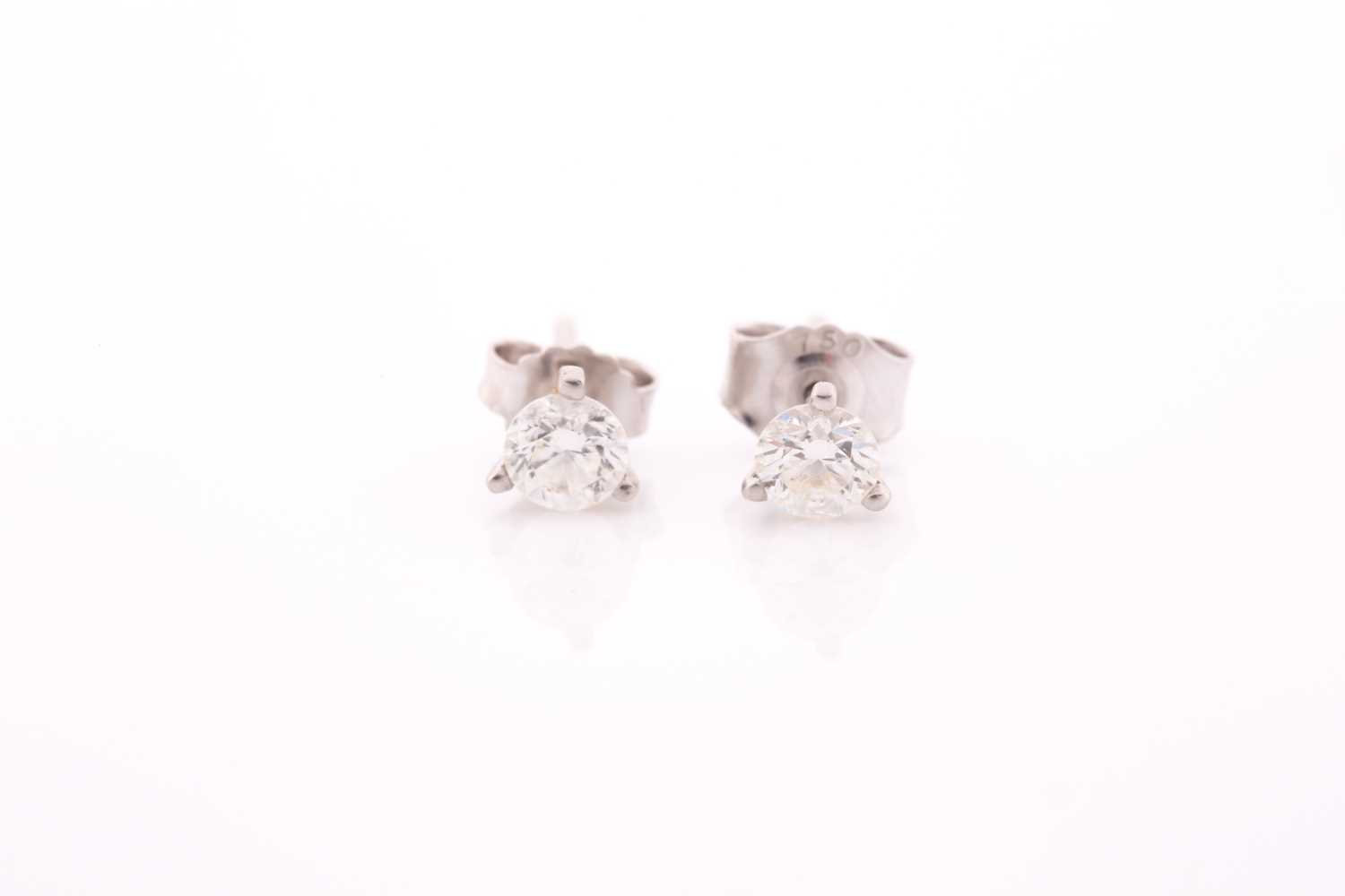 A pair of solitaire diamond stud earrings, set with round brilliant-cut diamonds of approximately
