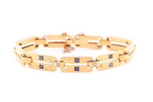 A yellow metal, diamond and sapphire bracelet, comprised of articulated bar links, the three