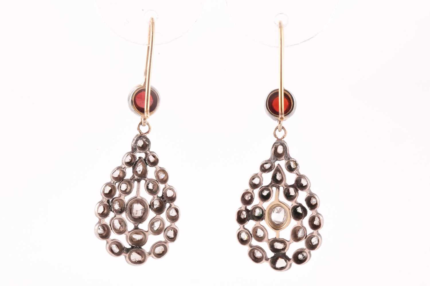 A pair of diamond and garnet earrings, the openwork pear-shaped silver mounts inset with rose-cut - Image 2 of 2