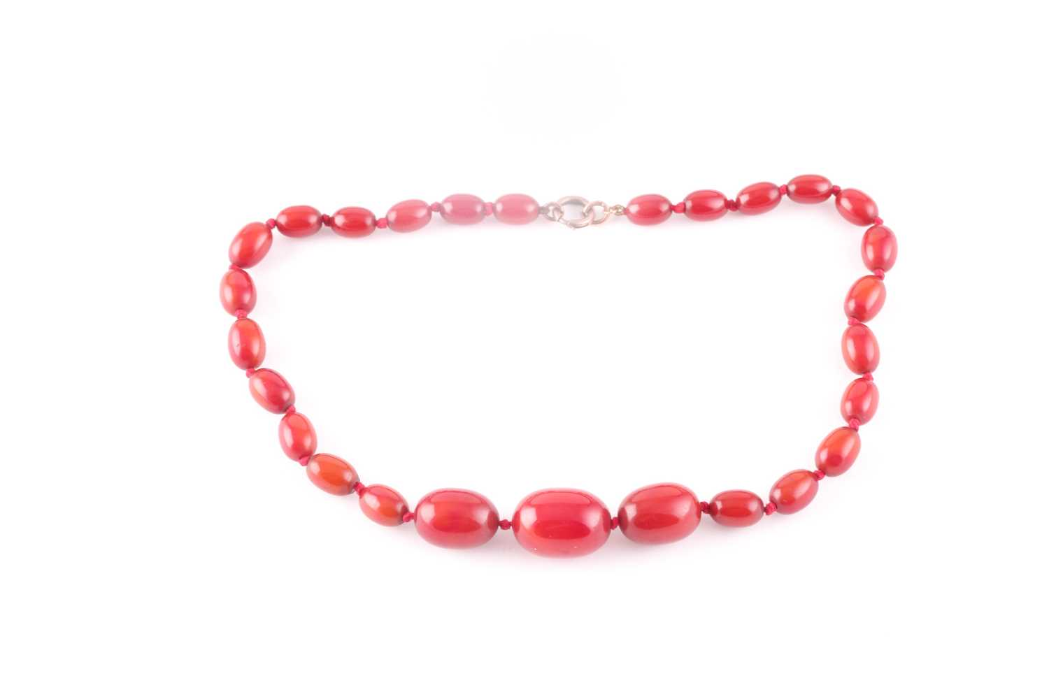 A cherry coloured Bakelite amber style bead necklace, comprised of oval beads, largest bead 21 mm,