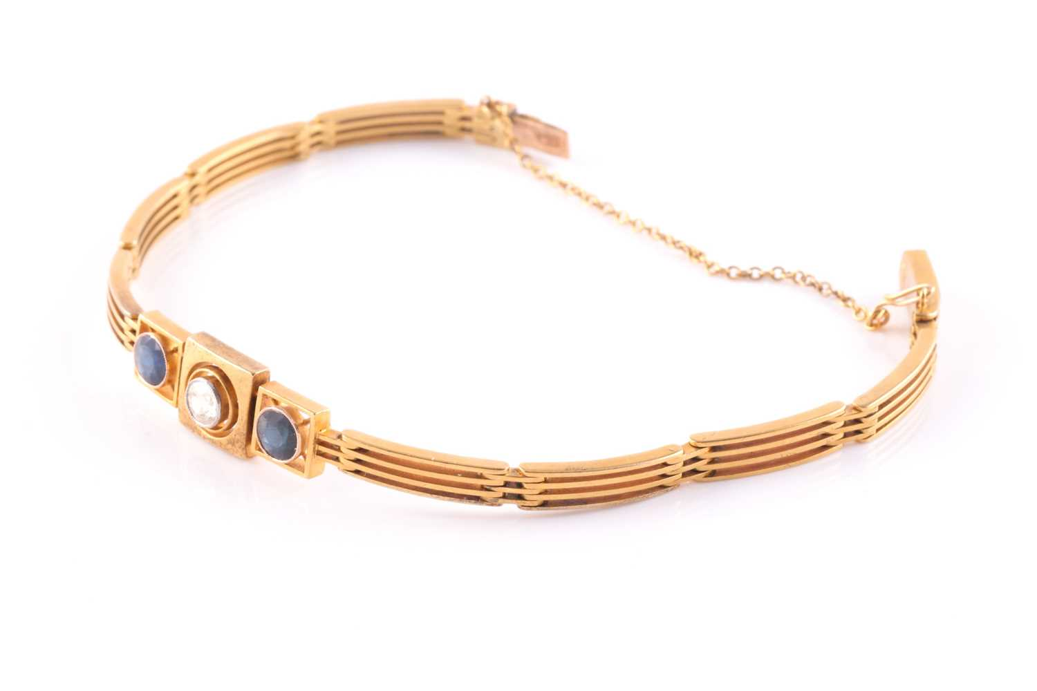A yellow metal, diamond, and sapphire bracelet, set with a round-cut diamond of approximately 0.33 - Image 3 of 5
