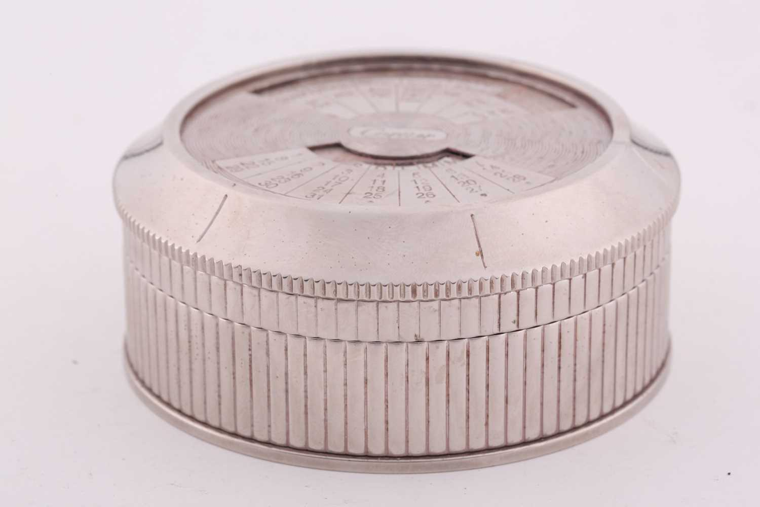 A Cartier chrome desk calender, with adjustable year, month, and date dial to lid, 8 cm diameter, - Image 2 of 5