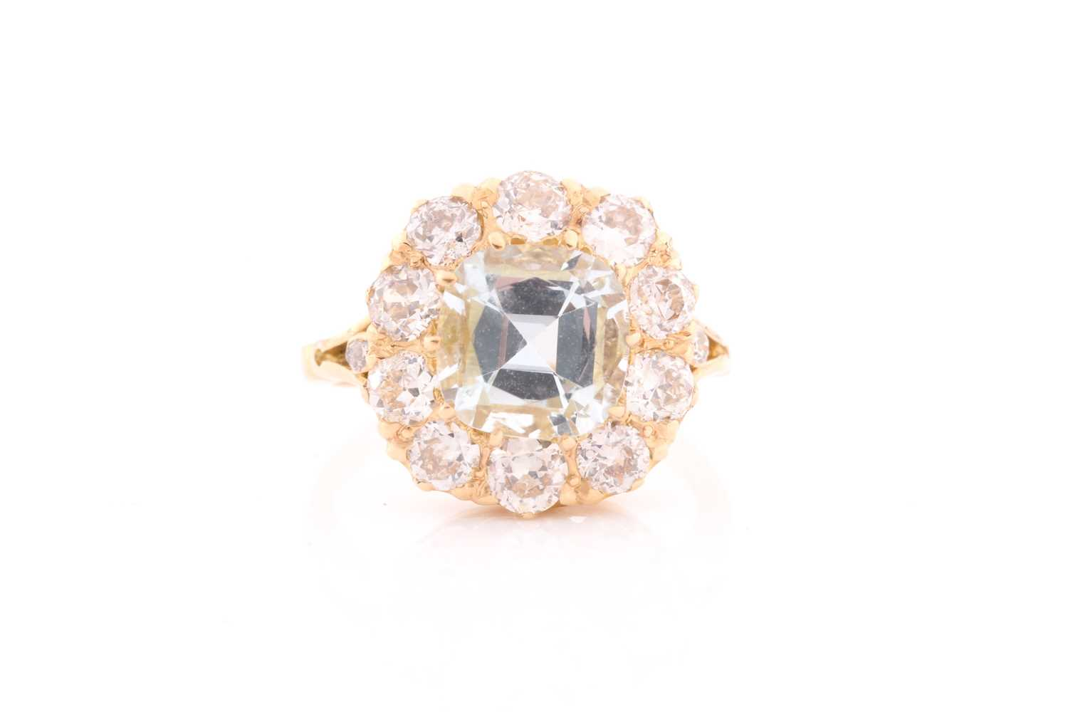 An 18ct yellow gold, diamond, and aquamarine cluster ring, set with a cushion-cut aquamarine of