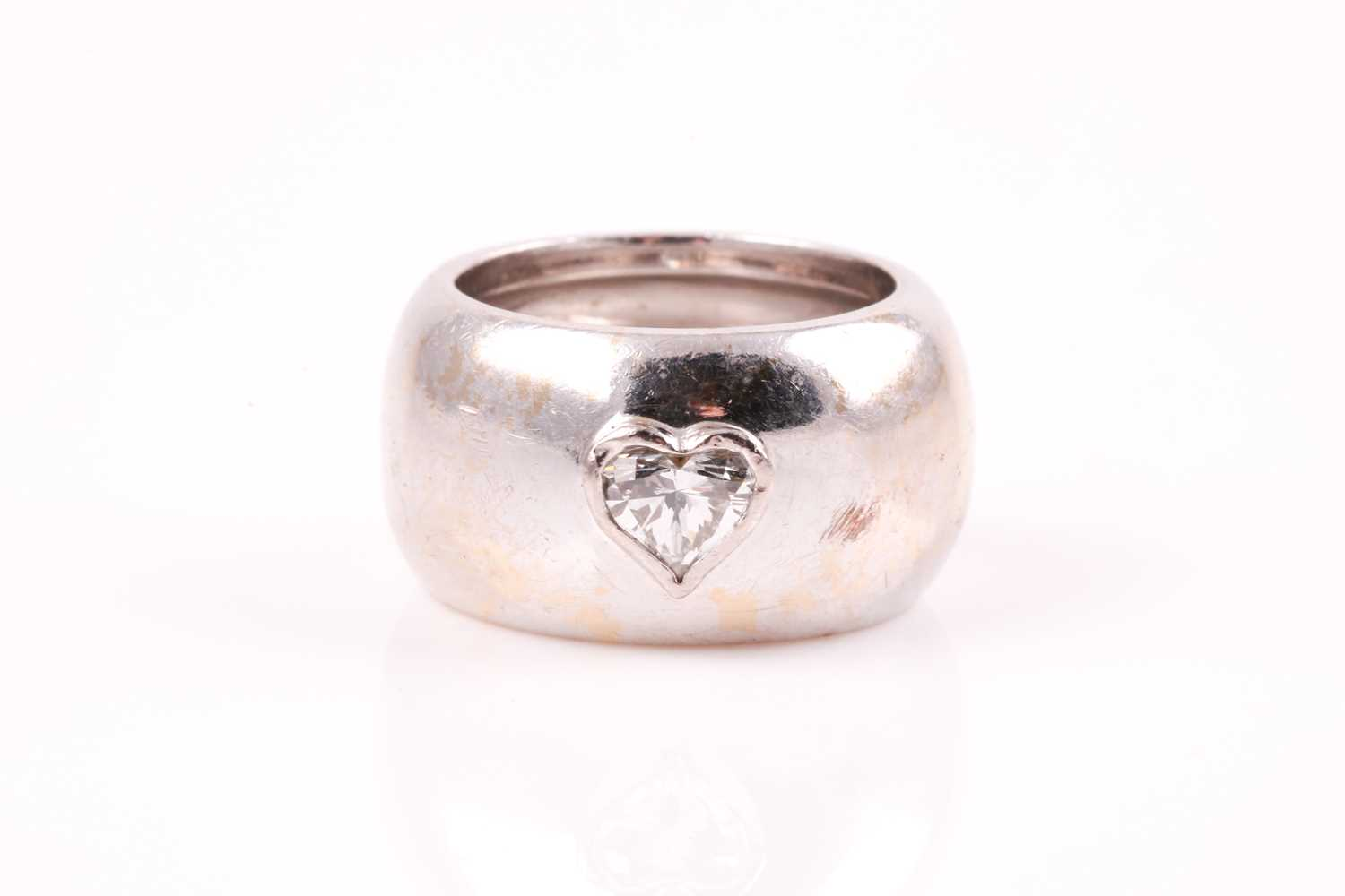 A single stone diamond dress ring, the heart-shaped diamond in raised rub-over mount within a wide