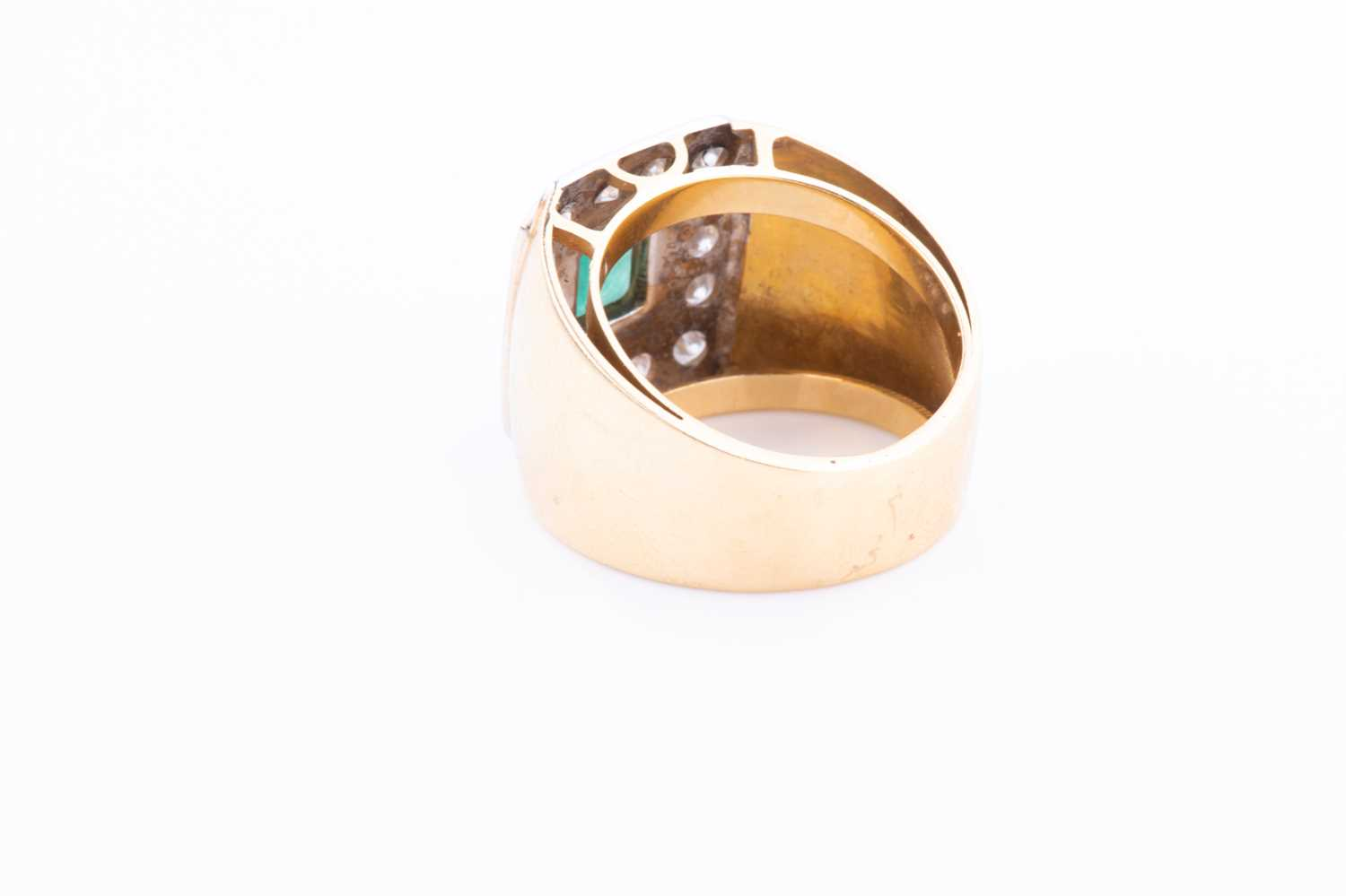 A yellow metal, diamond and emerald ring, centred with a bezel-set emerald, within a chamfered - Image 2 of 3