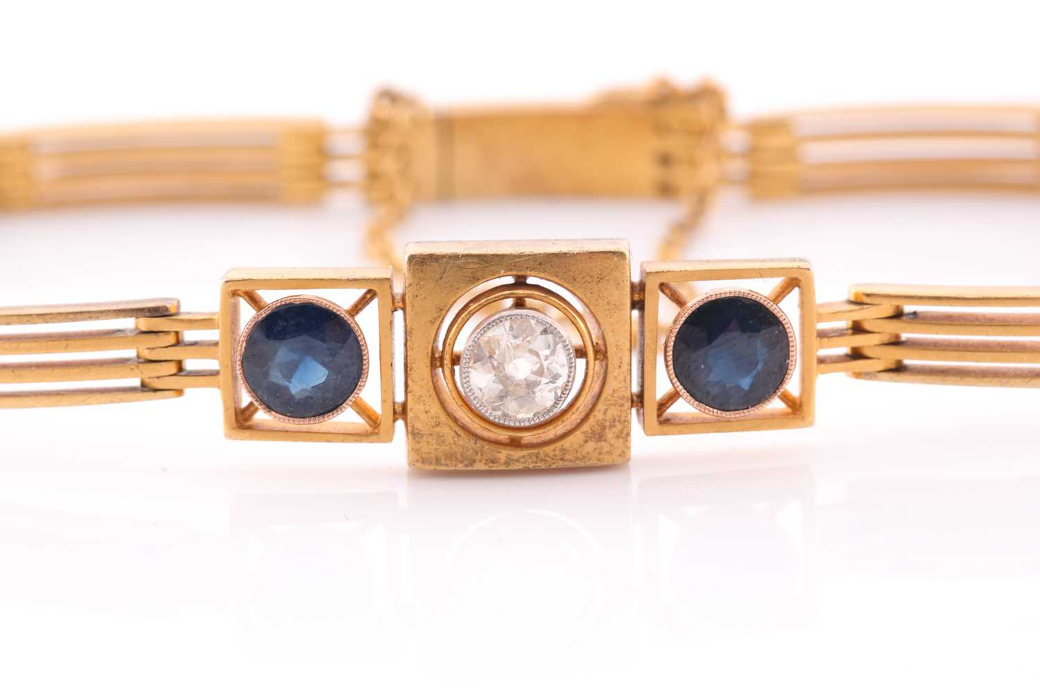 A yellow metal, diamond, and sapphire bracelet, set with a round-cut diamond of approximately 0.33 - Image 2 of 5