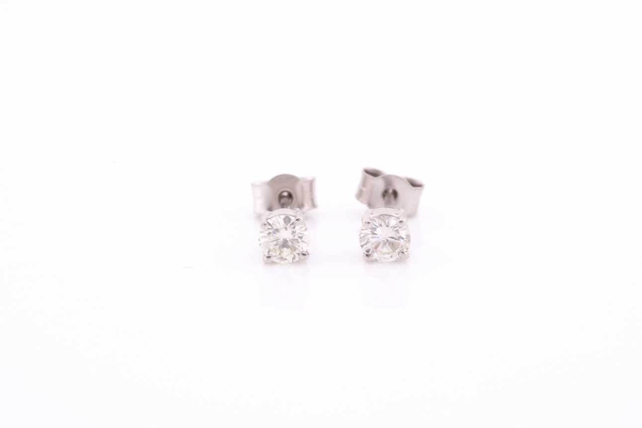A pair of platinum and diamond earrings, the round brilliant-cut diamonds of approximately 0.67 - Image 2 of 4