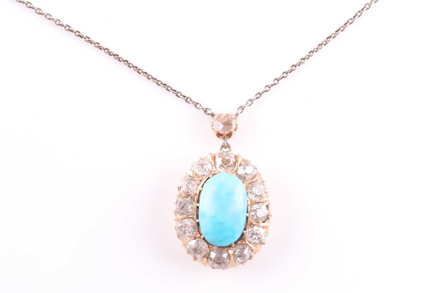 A diamond and turquoise cluster pendant, set with an oval turquoise plaque, surrounded with old-