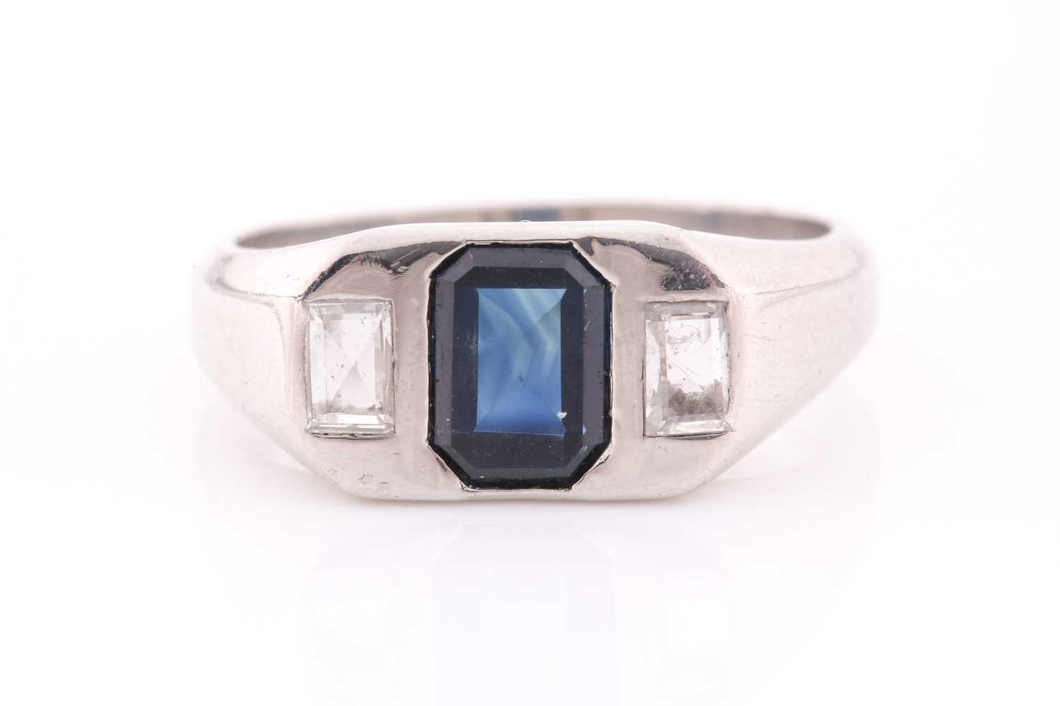 A diamond and sapphire ring, set with a mixed rectangular-cut sapphire, flanked with two modified