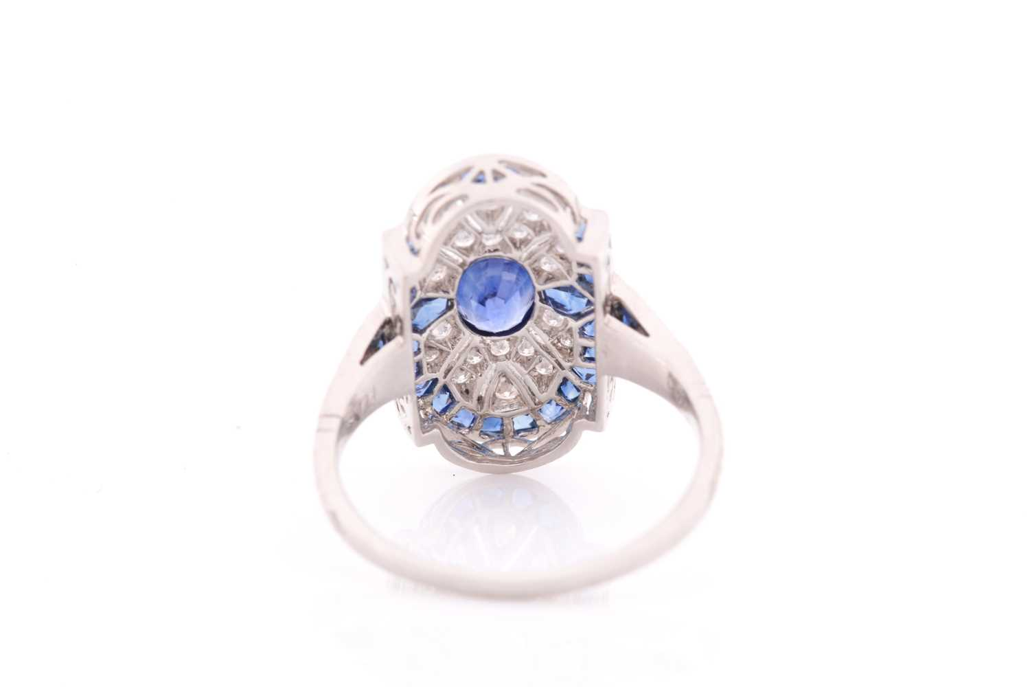 A platinum, diamond, and sapphire plaque ring, in the Art Deco style, centred with a mixed oval- - Image 4 of 4