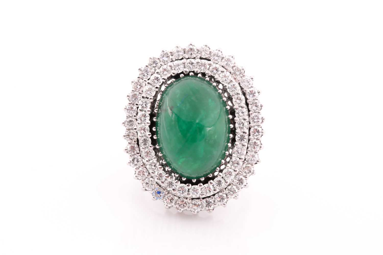 A diamond and emerald cocktail ring, circa 1960s, centred with an oval cabochon emerald, measuring