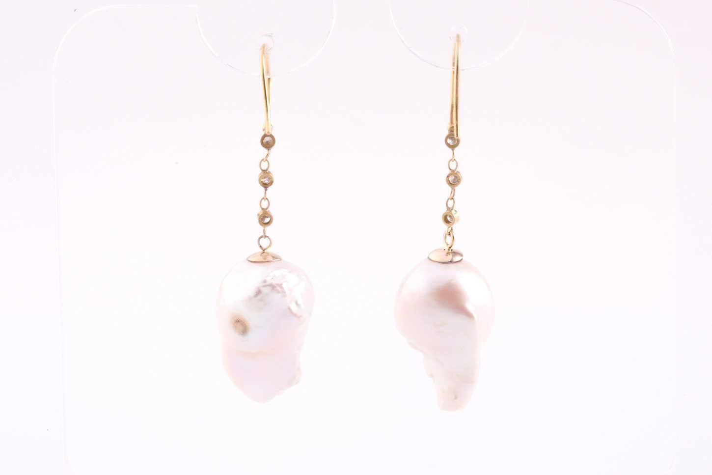 A pair of Baroque pearl and diamond drop earrings, the pearls drill mounted beneath a chain of three