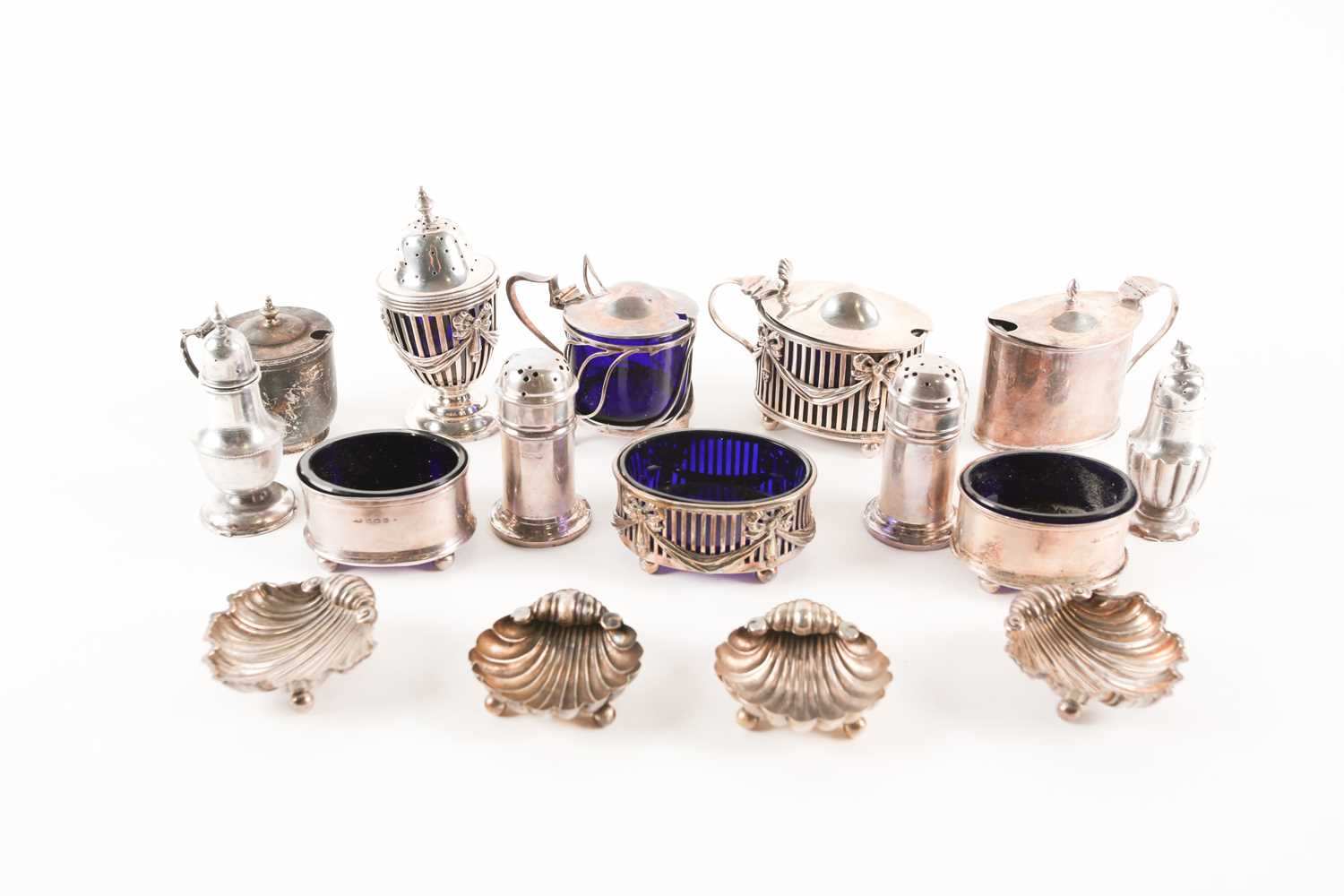A collection of silver cruet items including lidded mustards, peppers and salts. Mixed makers and