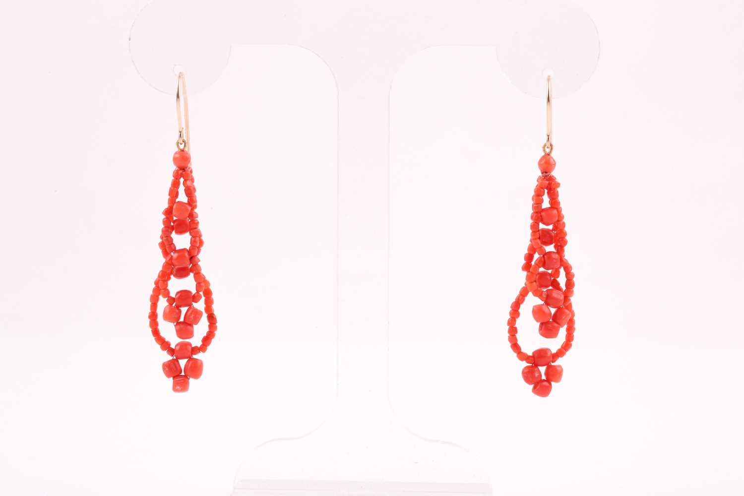 A pair of yellow metal and coral beaded earrings, the coral beads strung into two strands,