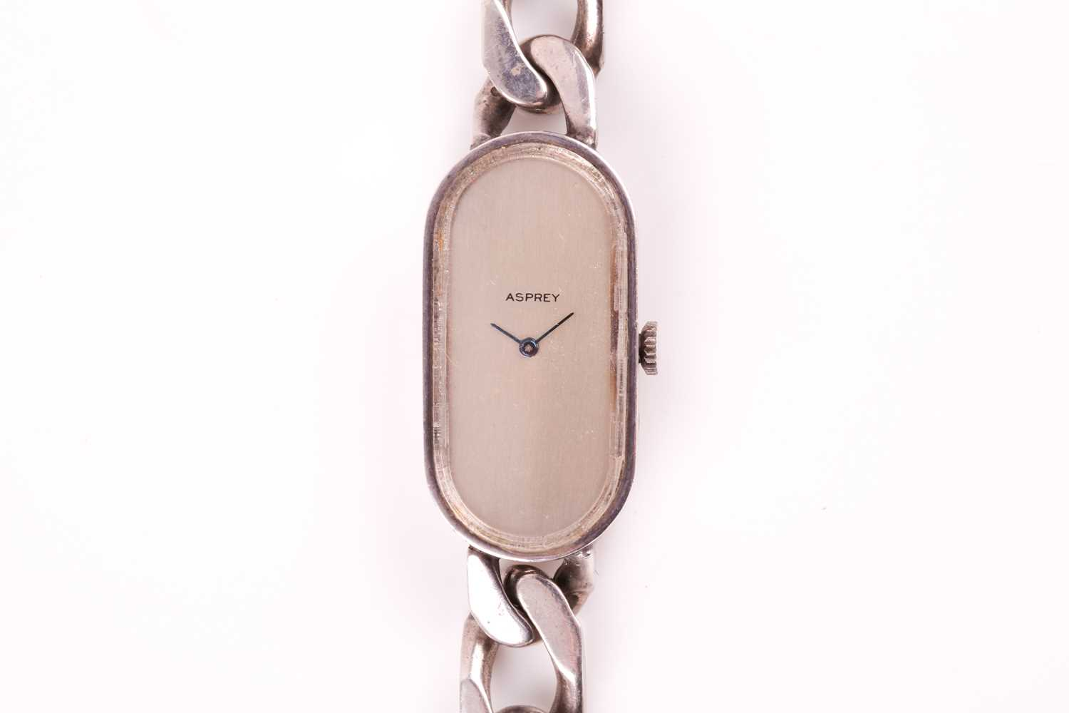 Asprey. A lady's silver wristwatch, the elongated oval brushed silvered dial with simple arrowhead