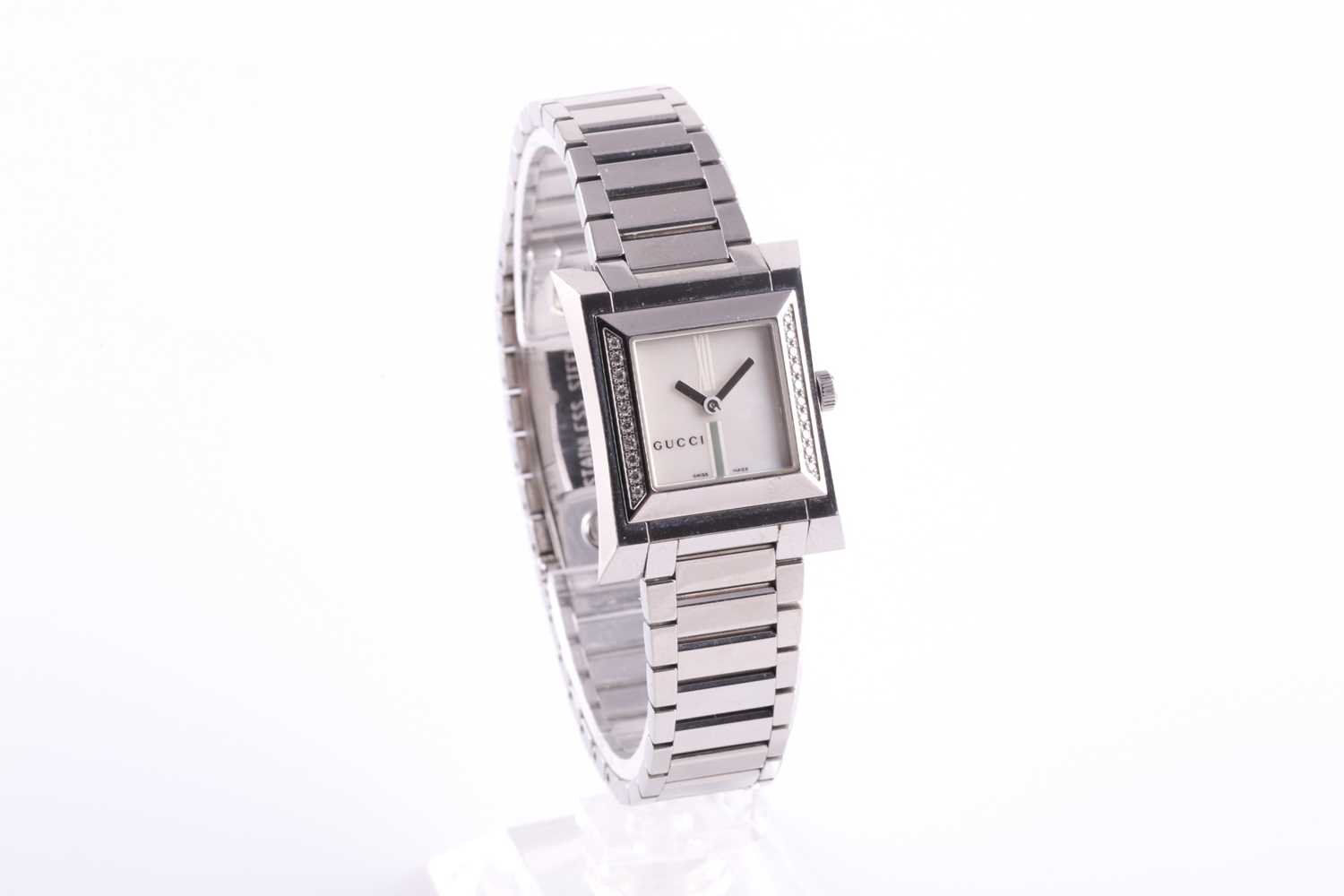 A ladies stainless steel watch by Gucci, with mother-of-pearl square dial, small diamonds set to