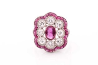 A platinum, diamond, and ruby ring, the stylised mount centred with a mixed oval-cut ruby within a