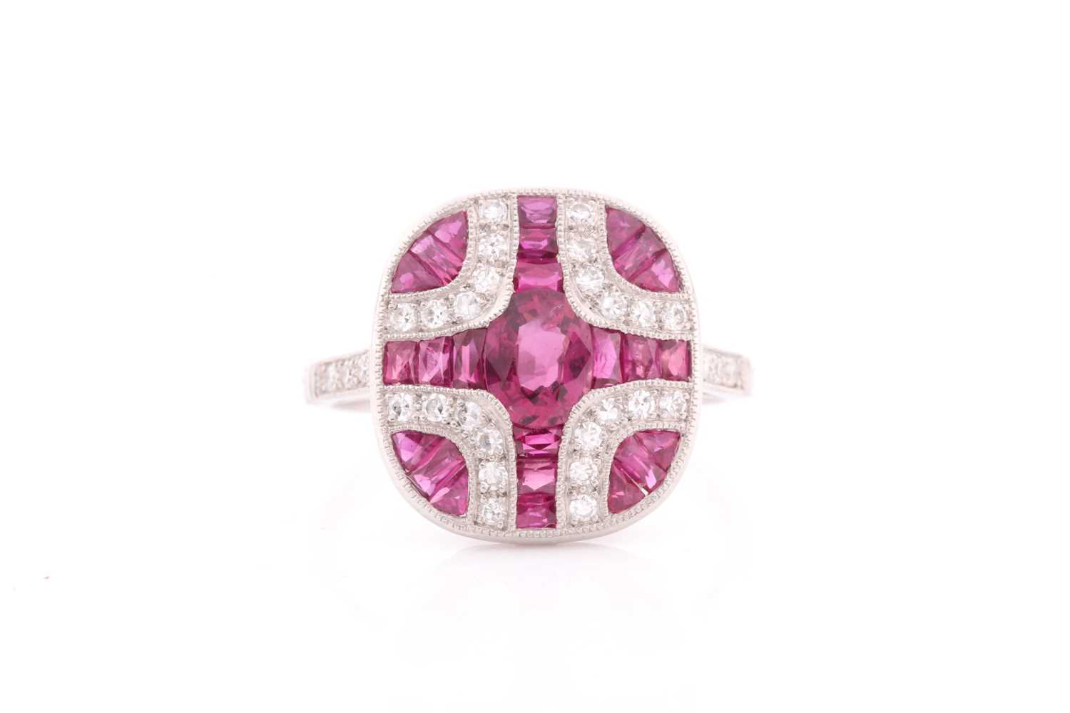 A platinum, diamond, and ruby ring, the rounded mount calibre-set with a mixed oval-cut ruby
